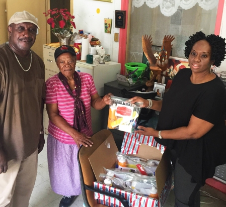 "Mr. Alvin A. Henley – District Manager, Catholic Charities of the Virgin Islands and ""Ms. B"" – Bethlehem House receive holiday care packages from viNGN's Yvonne Fenton"